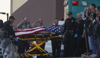 Law enforcement officers salute as the body of a Bay Area Rapid Transit police officer draped with the American flag is loaded into an Alameda County Sheriff's Coroner vehicle at Eden Medical Center in Castro Valley, Calif., Tuesday, Jan. 21, 2014. The officer was shot while serving a probation search warrant at a residence in Dublin, Calif., according to authorities. (AP Photo/The Contra Costa Times, Anda Chu)