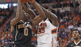Wake Forest's Codi Miller-McIntyre (0) attempts a shot as Clemson's Josh Smith defends during an NCAA college basketball game in Clemson, S.C. on Saturday, Jan. 18, 2014. (AP Photo/Anderson Independent-Mail, Mark Crammer) GREENVILLE NEWS OUT  SENECA OUT
