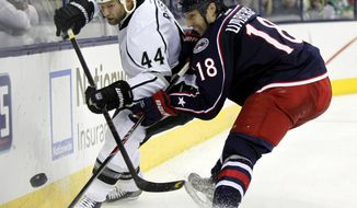 Columbus Blue Jackets' R.J. Umberger, right, works against Los Angeles Kings' Robyn Regehr, of Brazil, in the second period of an NHL hockey game in Columbus, Ohio, Tuesday, Jan. 21, 2014. (AP Photo/Paul Vernon)