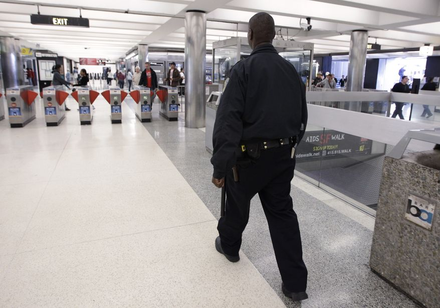 **FILE** In this Aug. 26, 2011 photo, a Bay Area Rapid Transit (BART) police officer walks around the Civic Center stop in San Francisco. (AP Photo/Paul Sakuma)