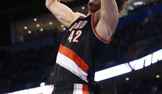 Portland Trail Blazers center Robin Lopez (42) dunks in front of Oklahoma City Thunder center Kendrick Perkins (5) in the first quarter of an NBA basketball game in Oklahoma City, Tuesday, Jan. 21, 2014. (AP Photo/Sue Ogrocki)