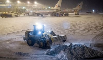Crews work to remove the snow from the tarmac at Reagan National Airport in Washington Tuesday evening, Jan. 21, 2014, after winter storm socked in the Mid-Atlantic region. (AP Photo/J. David Ake)