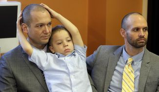 Plaintiffs Matthew Barraza, left, and his husband Tony Milner, right, look on as their son Jesse, 4, plays, during a news conference on Tuesday, Jan. 21, 2014, in Salt Lake City. The American Civil Liberties Union has sued the state of Utah over the issue of gay marriage, saying the official decision to stop granting benefits for newly married same-sex couples has created wrenching uncertainty. The lawsuit filed Tuesday says the state has put hundreds of gay and lesbian couples in legal limbo and prevented them from getting key protections for themselves and their children. (AP Photo/Rick Bowmer)