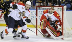 Florida Panthers defenseman Dmitry Kulikov (7), of Russia, clears the puck after a save by goaltender Tim Thomas (34) as Buffalo Sabres center Steve Ott (9) looks on during the first period of an NHL hockey game in Buffalo, N.Y., Tuesday, Jan. 21, 2014. (AP Photo/Gary Wiepert)