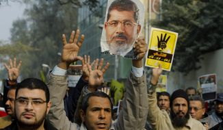 FILE - In this file photo taken Friday, Dec. 20, 2013, supporters of Egypt's ousted President Mohammed Morsi hold his poster as they raise their hands with four fingers, which has become a symbol for Morsi supporters, during a protest in Cairo, Egypt. While last week's constitutional referendum approved the draft charter, the low turnout - less than 39 percent - has put on display the country's enduring divisions six months after the ouster of Morsi and nearly three years after autocrat Hosni Mubarak was overthrown. (AP Photo/Amr Nabil, File)