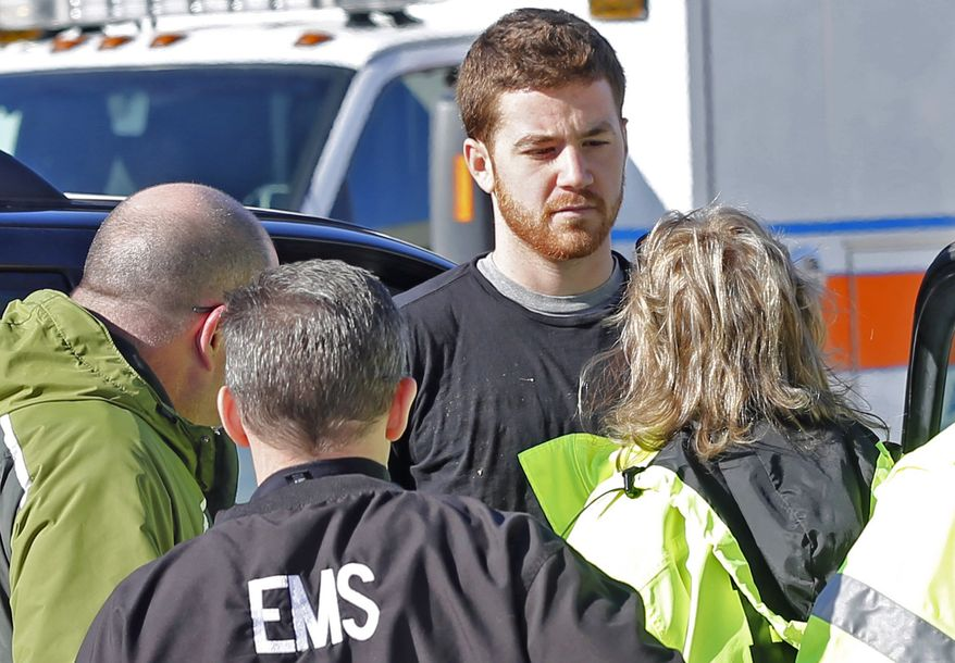 EMS personnel speak with an Cody Cousins, 23, who was detained after a shooting inside the Electrical Engineering building on the campus of Purdue University in West Lafayette, Ind. Cousins, of Warsaw, Ind., is being held in the Tippecanoe County Jail on a preliminary charge of murder, accused of shooting 21-year-old Andrew Boldt of West Bend, Wis. (AP Photo/The Journal & Courier, John Terhune)