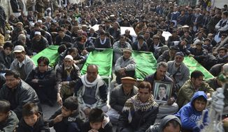 Relatives and mourners of  Shiite pilgrims who were killed on Tuesday by a bomb blast, protest sitting next to their bodies, in Quetta, Pakistan, Wednesday, Jan. 22, 2014. Shiite Muslims in Baluchistan protested Wednesday in Quetta, the capital of Baluchistan, demanding action to stop the continued violence against their sect; they brought the coffins of many of the dead into the streets as part of their protest.  (AP Photo/Arshad Butt)