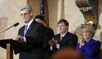 Mississippi Republican Gov. Phil Bryant receives a standing ovation from Lt. Gov. Tate Reeves, center, and his wife Deborah Bryant during his State of the State address before a joint session of the Legislature at the Capitol in Jackson, Miss., Wednesday, Jan. 22, 2014.  (AP Photo/Rogelio V. Solis)