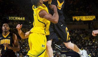 Iowa forward Aaron White, top, attempts a shot over Michigan forward Glenn Robinson III, in the second half of an NCAA college basketball game in Ann Arbor, Mich., Wednesday, Jan. 22, 2014. Michigan won 75-67. (AP Photo/Tony Ding)