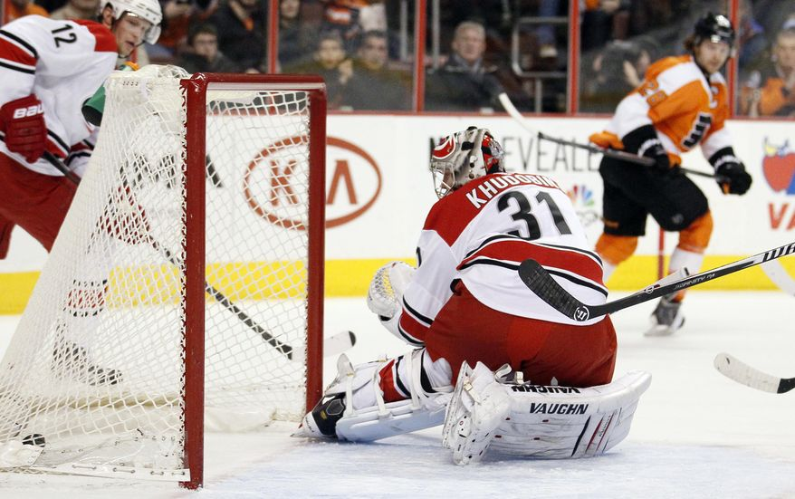 Carolina Hurricanes goalie Anton Khudobin, front, looks back at the puck in the net put there by Philadelphia Flyers' Claude Giroux, rear, during the second period of an NHL hockey game, Wednesday, Jan. 22, 2014, in Philadelphia. (AP Photo/Tom Mihalek)