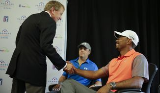 PGA Tour Commissioner Tim Finchem, left, greets Tiger Woods, right, and Jordan Spieth at the 2013 PGA Tour Player of the Year and Tour Rookie of the Year trophy presentation at the Farmers Insurance Open golf tournament at Torrey Pines Golf Course on Wednesday, Jan. 22, 2014 in San Diego. (AP Photo/Chris Carlson)