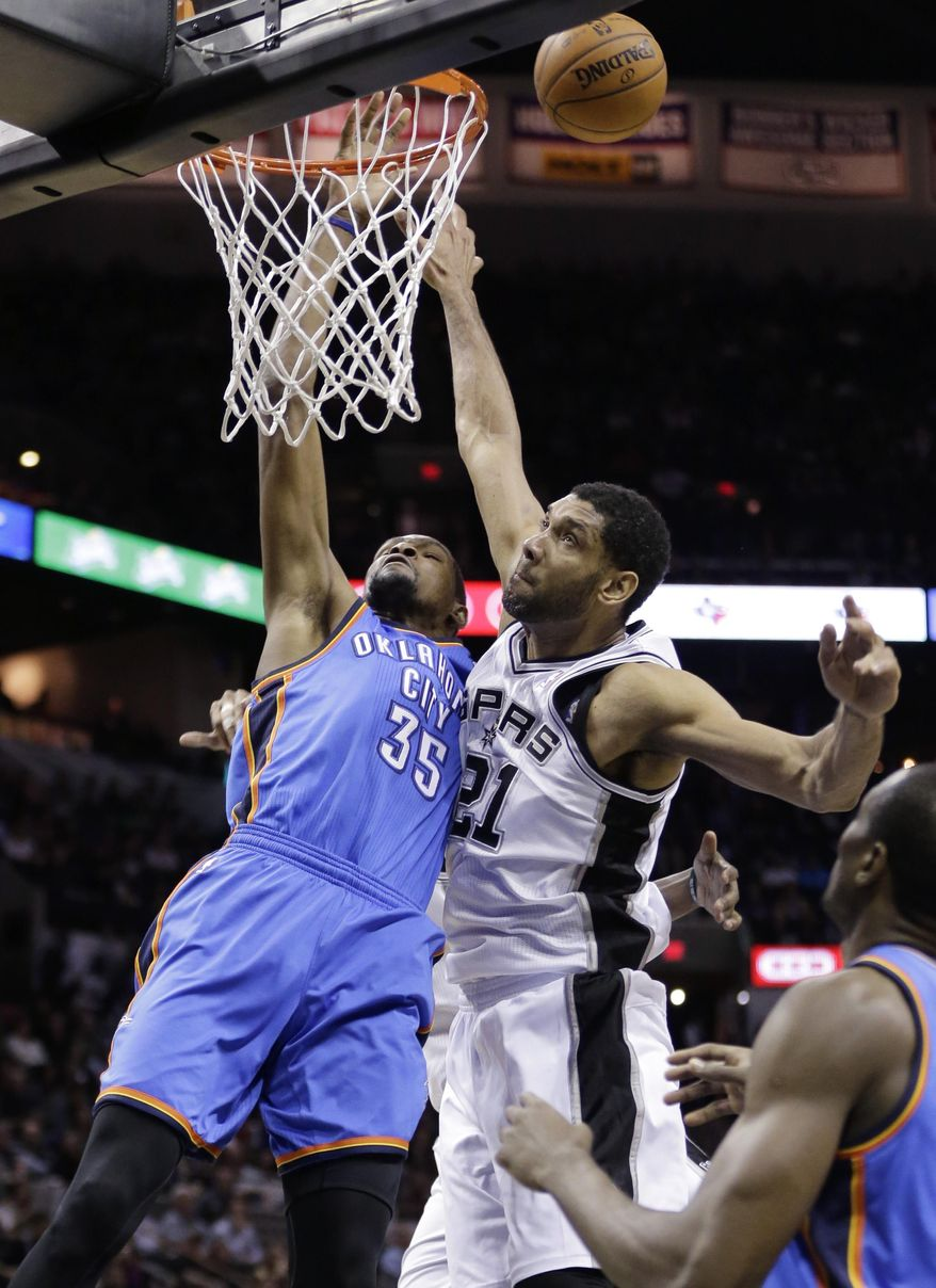 Oklahoma City Thunder's Kevin Durant (35) is fouled by San Antonio Spurs' Tim Duncan (21) during the second half of an NBA basketball game, Wednesday, Jan. 22, 2014, in San Antonio.  (AP Photo/Eric Gay)