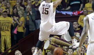 The student section cheers as Minnesota's Maurice Walker dunks in the first half of an NCAA college basketball game against Wisconsin, Wednesday, Jan. 22, 2014, in Minneapolis.   (AP Photo/Jim Mone)