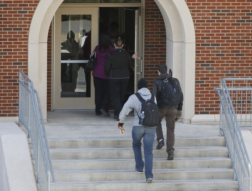 People enter Gould Hall at the University of Oklahoma in Norman, Okla., Wednesday, Jan. 22, 2014, after the area was re-opened. The area had been closed down following reports of gunfire. (AP Photo/Sue Ogrocki)