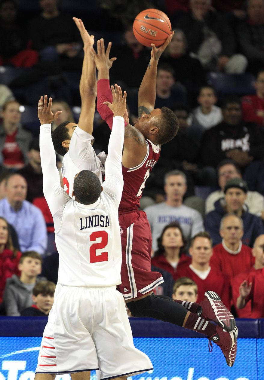 Massachusetts guard Derrick Gordon (2) takes a shot over Richmond guard Cedrick Lindsay (2) and forward Alonzo Nelson-Ododa (33) during the first half of an NCAA college basketball game in Richmond, Va., Wednesday, Jan. 22, 2014.  (AP Photo/Steve Helber)