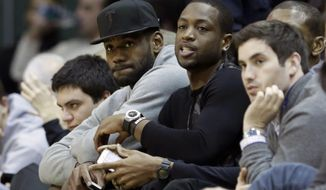 Miami Heat's LeBron James, left, and Dwyane Wade watch the NCAA basketball game between Duke and Miami during the second half of an NCAA basketball game in Coral Gables, Fla., Wednesday, Jan. 22, 2014. duke won 67-46. (AP Photo/Alan Diaz)