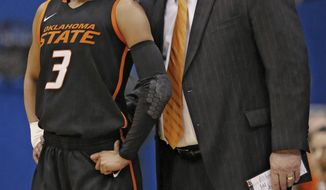 Oklahoma State head coach Jim Littell, right, talks with guard Tiffany Bias (3) during the first half of an NCAA college basketball game against Kansas in Lawrence, Kan., Wednesday, Jan. 22, 2014. (AP Photo/Orlin Wagner)
