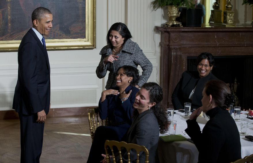 President Barack Obama laughs with women in the East Room of the White House in Washington, Wednesday, Jan. 22, 2014, as he leaves an event for the Council on Women and Girls, where he signed a memorandum creating a task force to respond to campus rapes. (AP Photo/Carolyn Kaster)