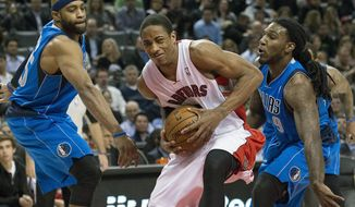 Toronto Raptors forward DeMar DeRozan, center, drives the middle past Dallas Mavericks forwards Vince Carter, left, and Jae Crowder during the first half of an NBA basketball game, Wednesday, Jan. 22, 2014 in Toronto.   (AP Photo/The Canadian Press, Nathan Denette)