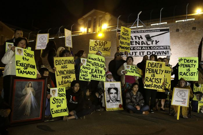 Protestors line up outside the prison walls just before receiving word that the scheduled execution of Mexican national Edgar Tamayo would proceed Wednesday, Jan. 22, 2014, in Huntsville, Texas . Tamayo was convicted