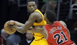 Chicago Bulls' Jimmy Butler (21) tries to poke the ball away from Cleveland Cavaliers' Luol Deng, of Sudan, in the second quarter of an NBA basketball game Wednesday, Jan. 22, 2014, in Cleveland. (AP Photo/Mark Duncan)