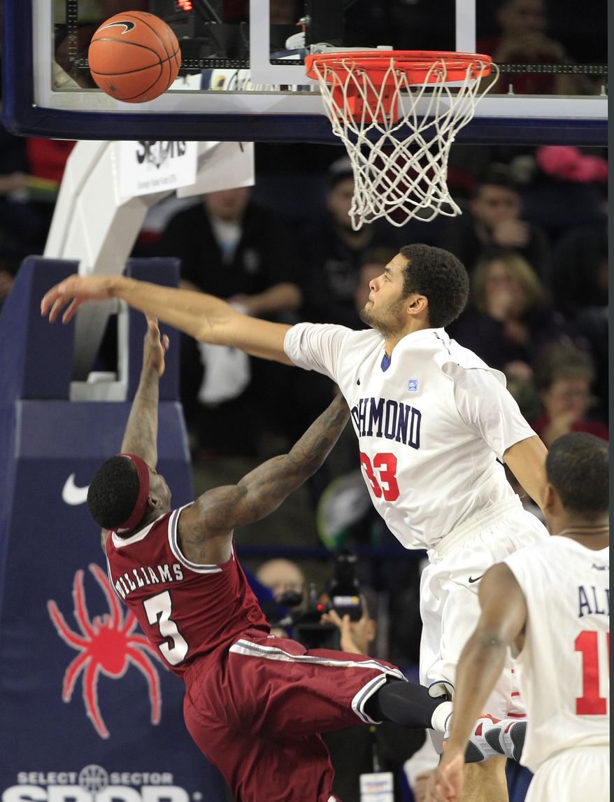Richmond forward Alonzo Nelson-Ododa (33) rejects a shot by Massachusetts guard Chaz Williams (3) during the first half of an NCAA college basketball game in Richmond, Va., Wednesday, Jan. 22, 2014.    (AP Photo/Steve Helber)