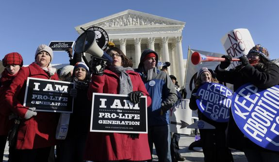 Pro-abortion and anti-abortion protestors rally outside the Supreme Court in Washington, Wednesday, Jan. 22, 2014, during the March for Life. Thousands of abortion opponents are facing wind chills in the single digits to rally and march on Capitol Hill to protest legalized abortion, with a signal of support from Pope Francis. (AP Photo/Susan Walsh)