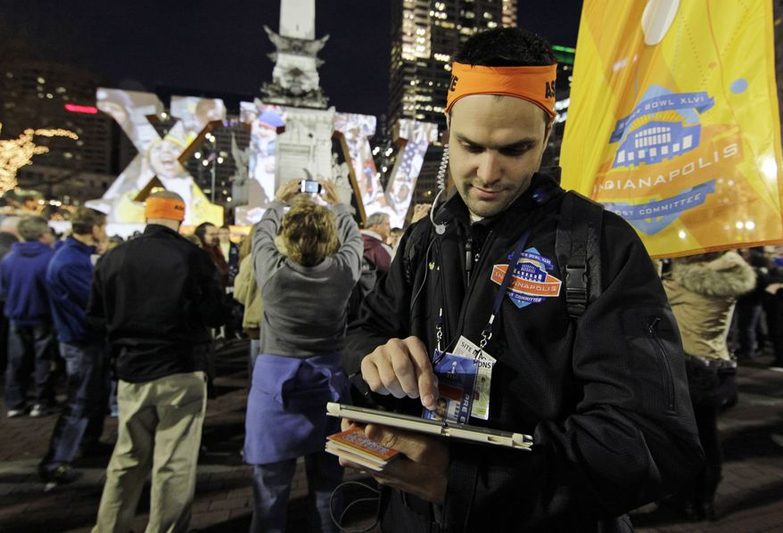 In this photo taken, Wednesday, Feb. 1, 2012, volunteer David Glenn post updates on social media for fans from Monument Circle during NFL football's Super Bowl XLVI events in Indianapolis.  A year after Super Bowl XLV set a record 4,064 tweets per second, organizers are aiming to make this year's game in Indianapolis the most connected ever. They'll achieve it by dispatching dozens of volunteers to downtown streets, armed with tablets and walkie-talkies that connect them to the game's first-ever social media command center. (AP Photo/Darron Cummings)