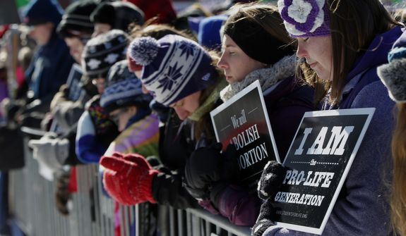 Anti-abortion demonstrators bow their heads in prayer on the National Mall in Washington, Wednesday, Jan. 22, 2014, during the annual March for Life. Thousands of anti-abortion demonstrators are gathering in Washington for an annual march to protest the Supreme Court's landmark 1973 decision that declared a constitutional right to abortion. (AP Photo/Charles Dharapak)
