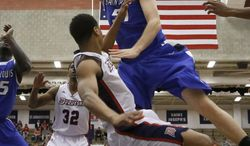 Saint Louis' Rob Loe, top, draws a foul as he goes over Duquesne's L.G. Gill to shoot during the first half of an NCAA college basketball game Wednesday, Jan. 22, 2014, in Pittsburgh. (AP Photo/Keith Srakocic)