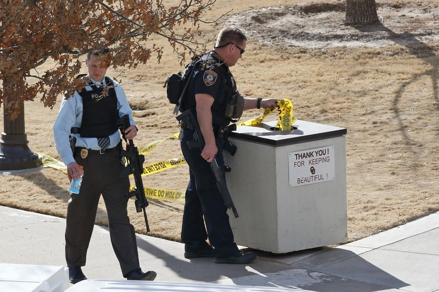 A police officer removes yellow police tape from the area surrounding Gould Hall at the University of Oklahoma in Norman, Okla., Wednesday, Jan. 22, 2014. The University of Oklahoma says authorities found no evidence of shots being fired on campus and no injuries have been reported. (AP Photo/Sue Ogrocki)