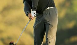 CORRECTS TO FIFTH HOLE, NOT THE FOURTH HOLE - Tiger Woods hits his tee shot on the fifth hole during the pro-am at the Farmers Insurance Open golf tournament at Torrey Pines Golf Course on Wednesday, Jan. 22, 2014, in San Diego. (AP Photo/Chris Carlson)