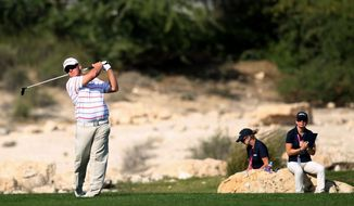 George Coetzee of South Africa hits his tee shot on the 7th hole during the first round of the Commercial Bank Qatar Masters at the Doha Golf Club in Doha, Qatar, Wednesday, Jan. 22, 2014. (AP Photo/Osama Faisal)
