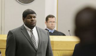 Former Dallas Cowboys Josh Brent stands in court as potential jurors are directed into Judge Robert Burns, looking on in back,  courtroom Friday, Jan. 10, 2014, in Dallas.  (AP Photo/LM Otero)
