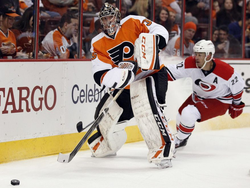 Philadelphia Flyers' Steve Mason moves the puck out from behind the net as Carolina Hurricanes' Manny Malhotra trails, during the first period of an NHL hockey game, Wednesday, Jan. 22, 2014, in Philadelphia. (AP Photo/Tom Mihalek)