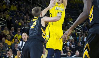 Iowa guard Josh Oglesby (2) defends a 3-pointer from Michigan guard Nik Stauskas in the first half of an NCAA college basketball game in Ann Arbor, Mich., Wednesday, Jan. 22, 2014. (AP Photo/Tony Ding)