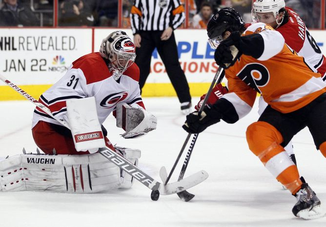 Philadelphia Flyers' Matt Read, right,  brings the puck in as Carolina Hurricanes goalie Anton Khudobin, left, defends during the second period of an NHL hockey game, Wednesday, Jan. 22, 2014, in Philadelphia. (AP Photo/Tom Mihalek)