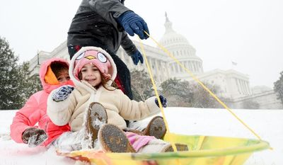 Brian Darling of Washington, D.C. takes his two daughters Julie, 5, and Kathleen, 2, sledding on the west lawn of the U.S. Capitol Building as snow accumulates in the Washington region, Washington, D.C., Tuesday, January 21, 2014. (Andrew Harnik/The Washington Times)