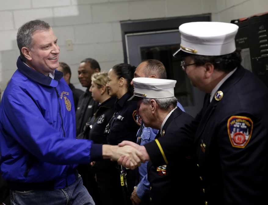 ** FILE ** New York City Mayor Bill de Blasio, left, greets emergency personnel before a news conference about snow removal in the Brooklyn borough of New York, Wednesday, Jan. 22, 2014. (AP Photo/Seth Wenig)