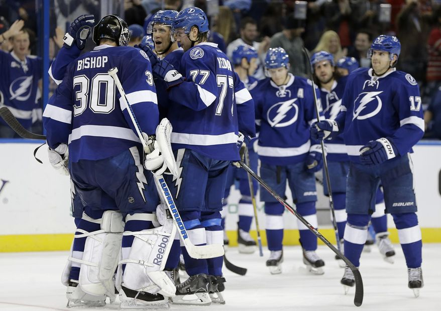 Tampa Bay Lightning goalie Ben Bishop (30) celebrates with teammates, including Victor Hedman (77), of Sweden, after stopping all the Ottawa Senators shots during a shootout in an NHL hockey game Thursday, Jan. 23, 2014, in Tampa, Fla. The Lightning won the game 4-3. (AP Photo/Chris O'Meara)