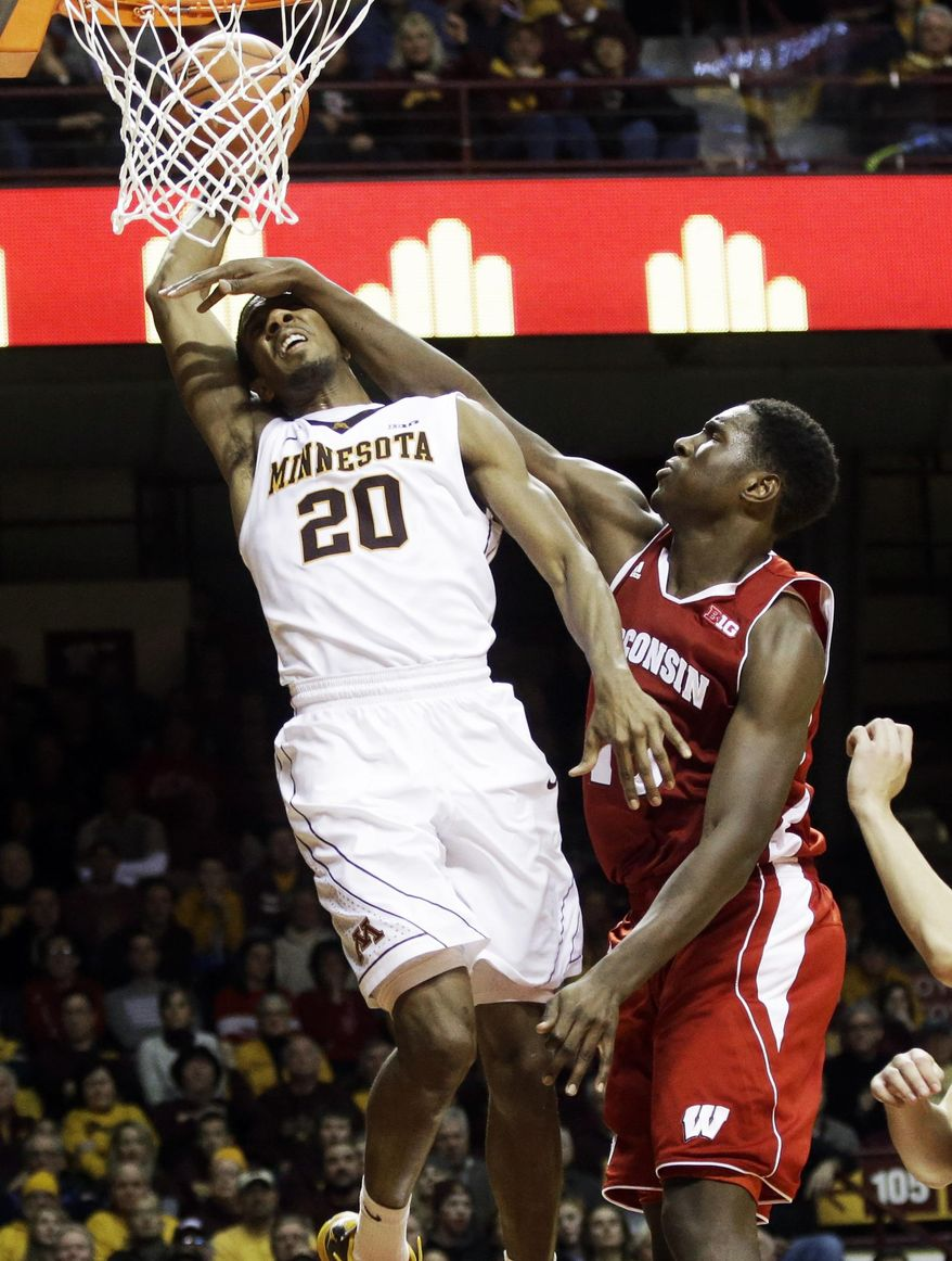 Minnesota's Austin Hollins, left, is fouled by Wisconsin's Nigel Hayes but manages to dunk the ball in the second half of an NCAA college basketball game, Wednesday, Jan. 22, 2014, in Minneapolis. Minnesota won 81-68. (AP Photo/Jim Mone)