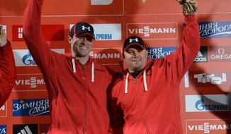 Winner Steven Holcomb, left,  and Steven Langton of the U.S. celebrate on the podium after  the two-men bob race at the Bob World  Cup  in Innsbruck, Austria, on Saturday, Jan. 18. 2014. (AP Photo/Kerstin Joensson)