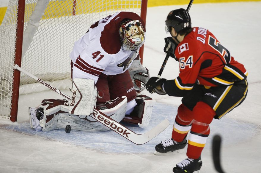 Phoenix Coyotes goalie Mike Smith, left, stops a shot from Calgary Flames' David Jones during first period NHL hockey action in Calgary, Canada, Wednesday, Jan. 22, 2014. (AP Photo/The Canadian Press, Jeff McIntosh)