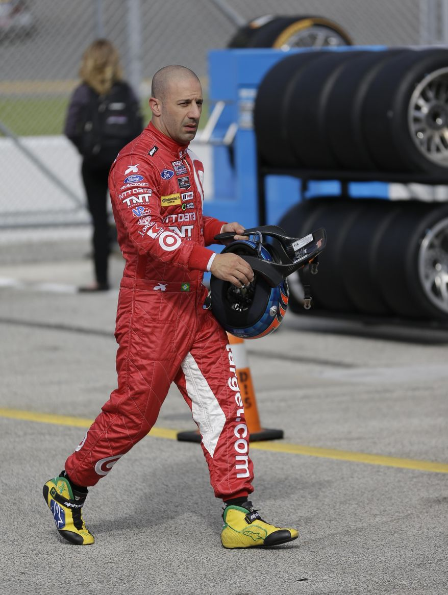 Driver Tony Kanaan, of Brazil, walks back to his garage after a practice session for the IMSA Series Rolex 24 hour auto race at Daytona International Speedway in Daytona Beach, Fla., Thursday, Jan. 23, 2014.(AP Photo/John Raoux)