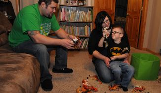 Benjamin Barron, left, and Danielle Barron play with their 3 year old son, Wilhelm who has a rare disease called Moebius Syndrome.  Moebius syndrome is a rare neurological disorder that is present at birth. It primarily affects nerves, leaving those with the condition unable to move parts of their face and unable to move their eyes laterally. (AP Photo/The Oshkosh Northwestern, Joe Sienkiewicz ) NO SALES