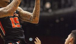 Oregon State forward Eric Moreland (15) draws a blocking foul on Washington State guard Dexter Kernich-Drew (10) during the second half of an NCAA college basketball game Wednesday, Jan. 22, 2014, at Beasley Coliseum in Pullman, Wash. Oregon State won 66-55. (AP Photo/Dean Hare)