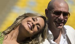 Brazilian singer Claudia Leitte and rapper Pitbull pose at the Maracana stadium in Rio de Janeiro, Brazil, Thursday, Jan. 23, 2014. Claudia Leitte and Pitbull  will perform with Jennifer Lopez the official song for the 2014 World Cup. Football's governing body didn't elaborate when the song, written and co-produced by Pitbull will be released. (AP Photo/Felipe Dana)