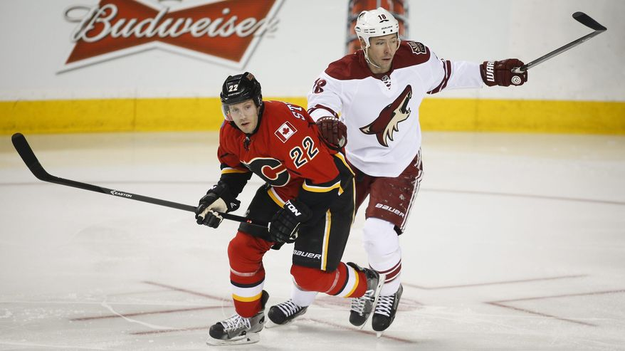 Phoenix Coyotes' David Moss, right, and Calgary Flames' Lee Stempniak chase the puck during first period NHL hockey action in Calgary, Canada, Wednesday, Jan. 22, 2014. (AP Photo/The Canadian Press, Jeff McIntosh)