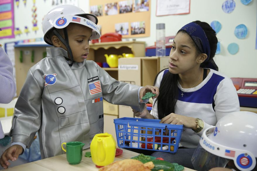 In this Tuesday, Jan. 21, 2014 photo, Bryson Payne, 4, left, and his teacher Jacqualine Sanchez play with pretend food in a pre-kindergarten class at the Sheltering Arms Learning Center in New York. Payne participated in a program that was produced in conjunction with Sesame Street to educate children about nutrition and health. (AP Photo/Seth Wenig)