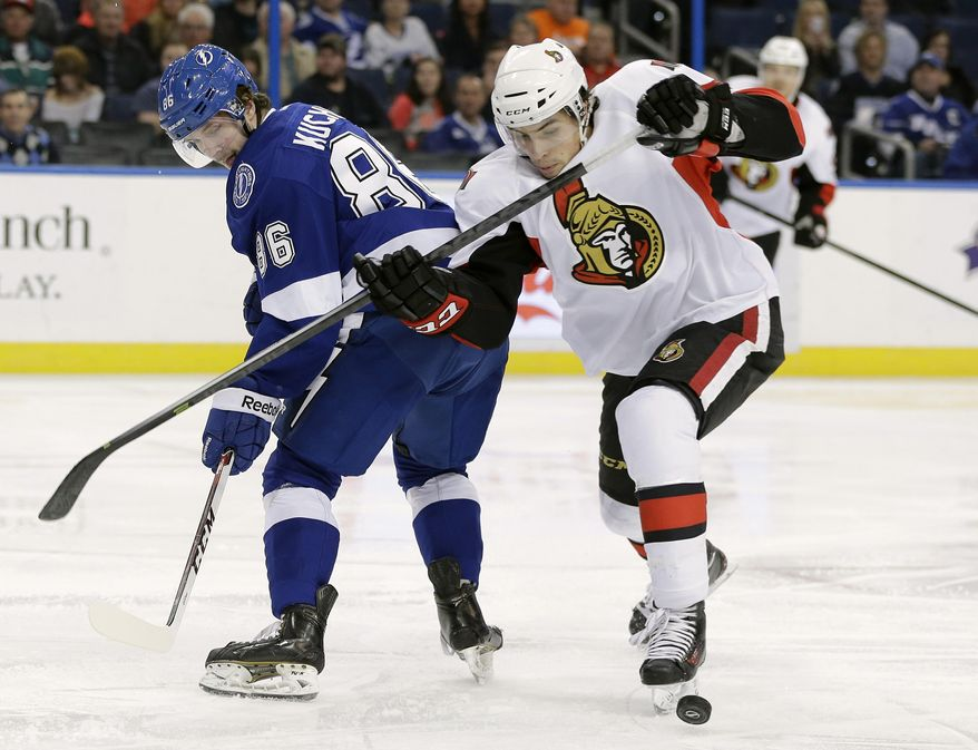 Ottawa Senators defenseman Cody Ceci, right,  ties up Tampa Bay Lightning right wing Nikita Kucherov, left, of Russia, during the second period of an NHL hockey game Thursday, Jan. 23, 2014, in Tampa, Fla. (AP Photo/Chris O'Meara)